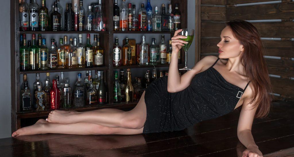 お酒を持ちカウンターで横になる美しい女性