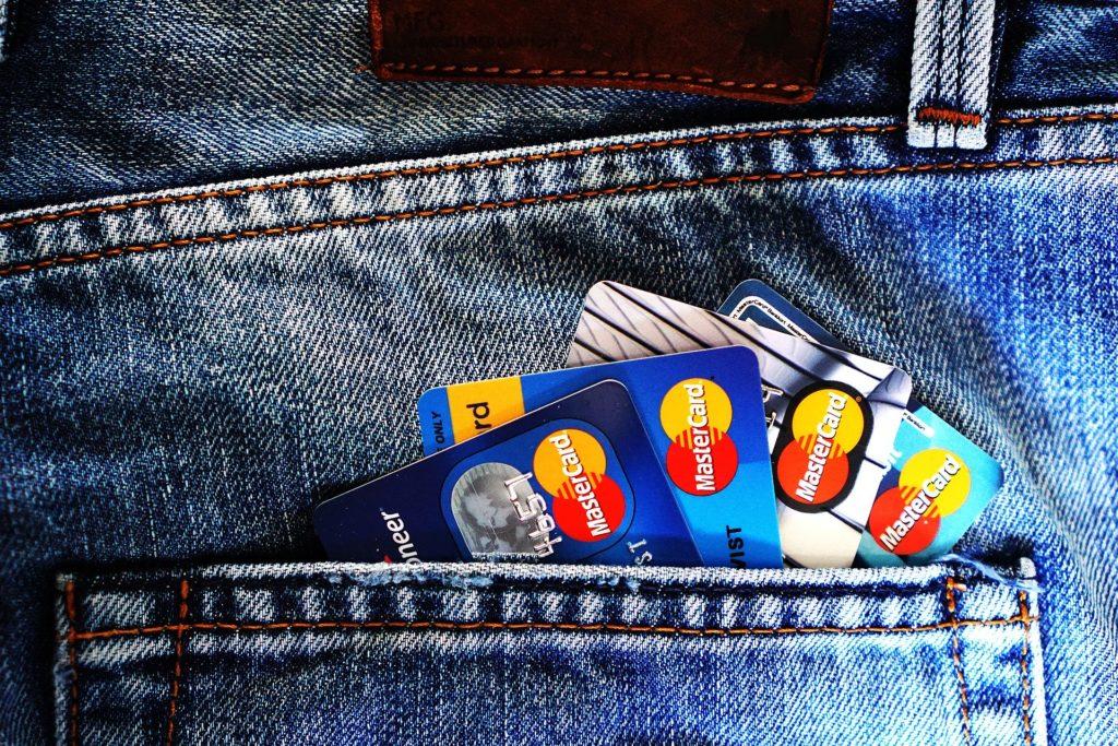 ジーンズの後ろポケットに入れられたクレジットカード4枚