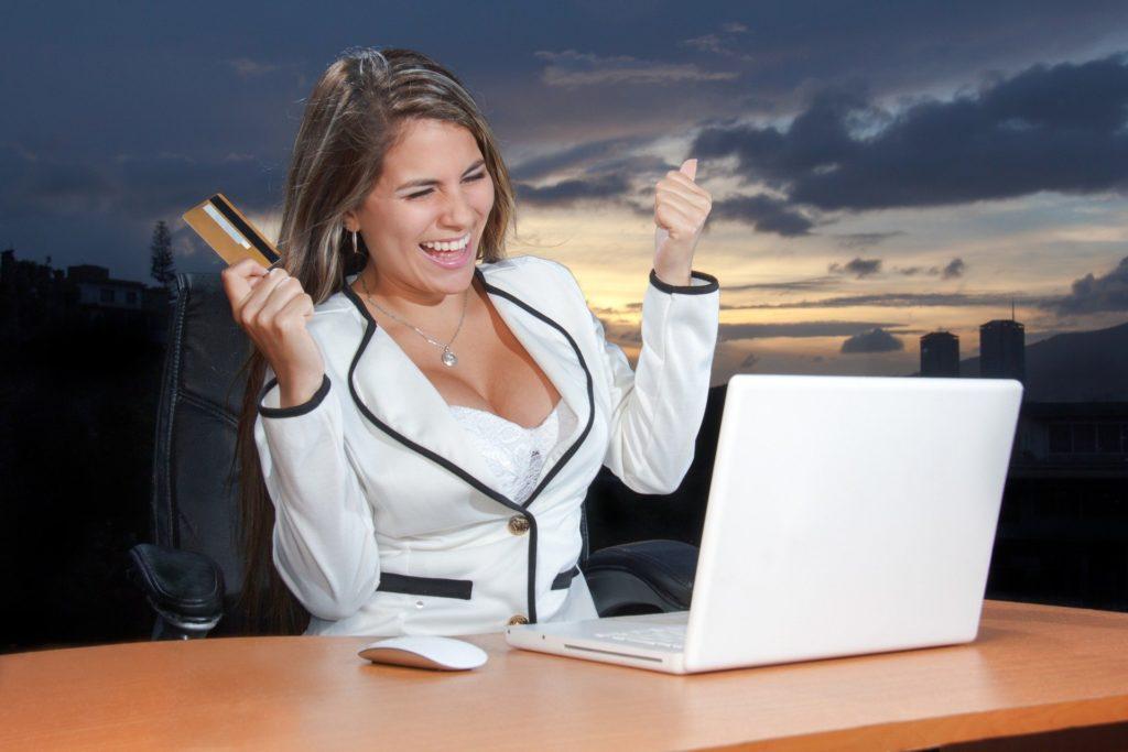 パソコンを前に喜んでいる女性