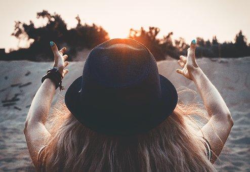 両手を太陽に捧げる女性の後ろ姿