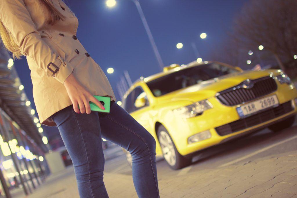 スマホを持った女性とタクシー