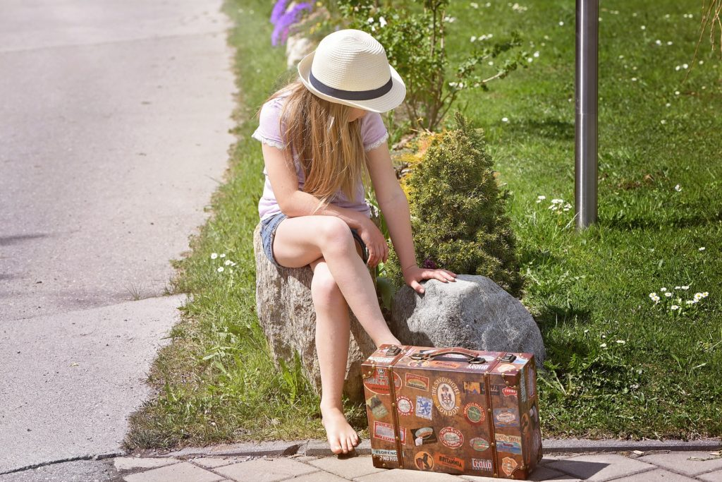 旅行かばんの隣で座る女性