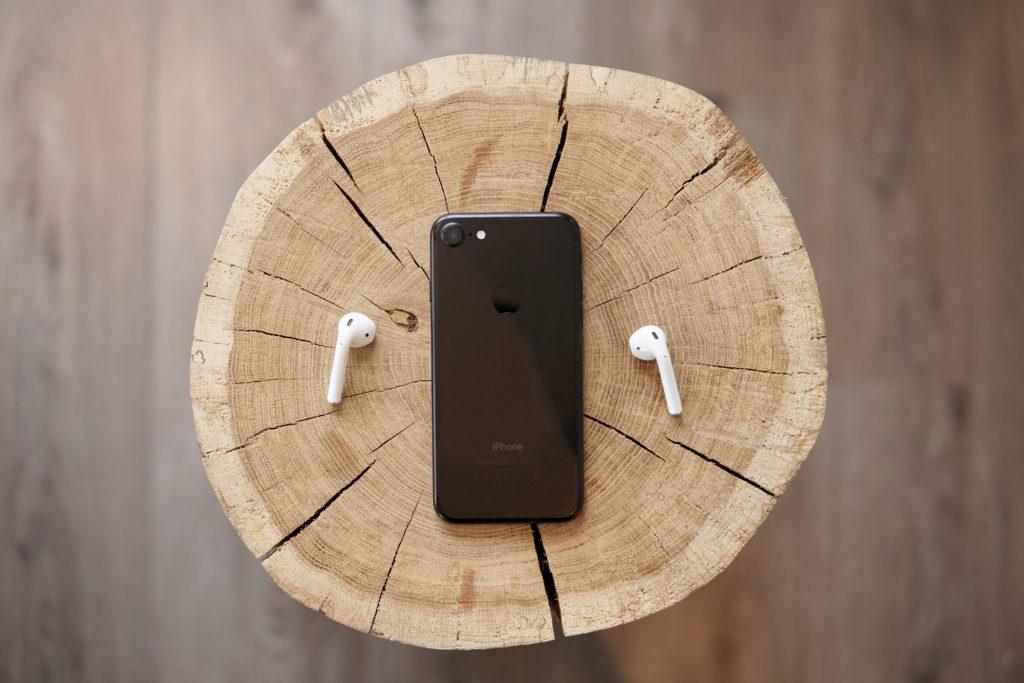 丸太の上に置かれたAirPodsとiPhone